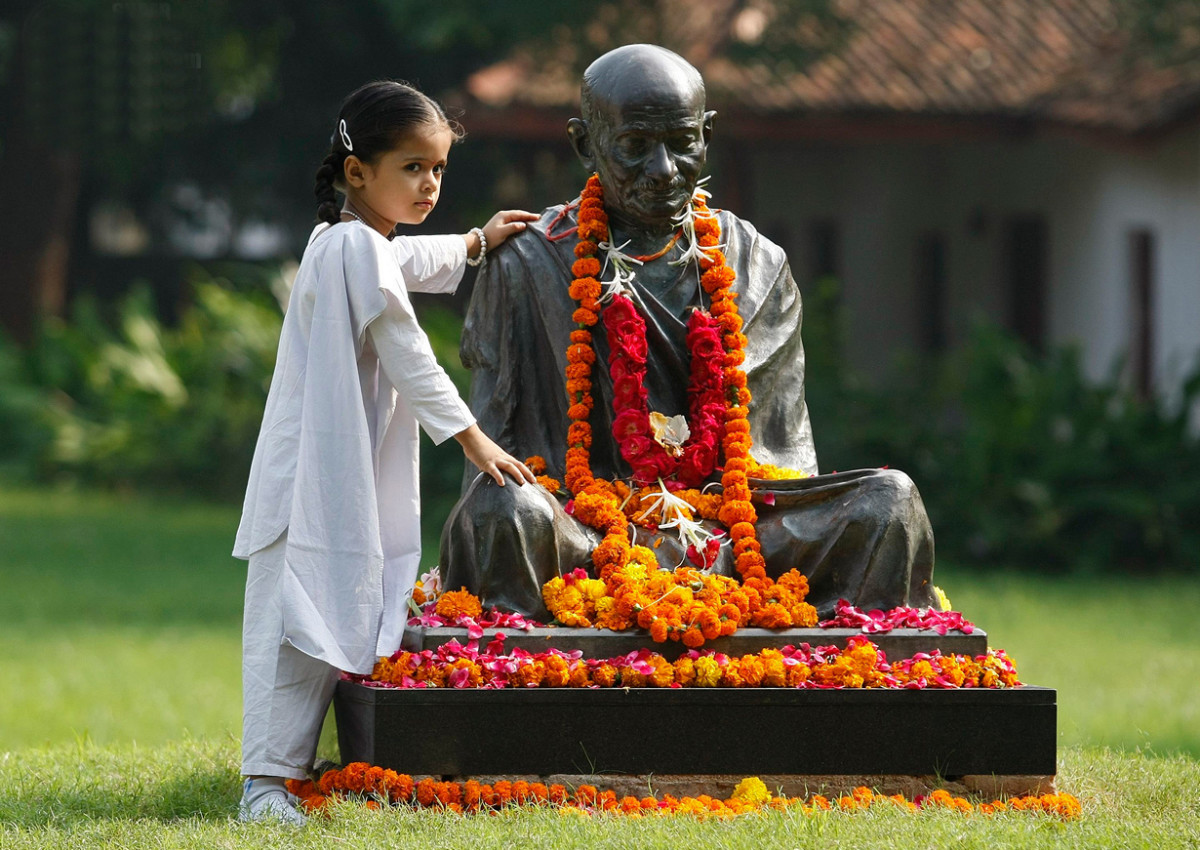 A schoolgirl poses for a picture next to a statue of Mahatma Gandhi during celebrations to mark the 144th birth anniversary of Gandhi, at Ahmedabad in the western Indian state of Gujarat October 2, 2013. Mahatma Gandhi, also known as the
